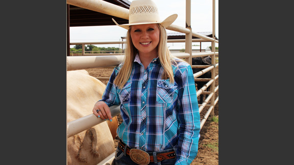 Paige Stout pictured standing next to bull, Recovery Time. (Photo by Jessica Crabtree)